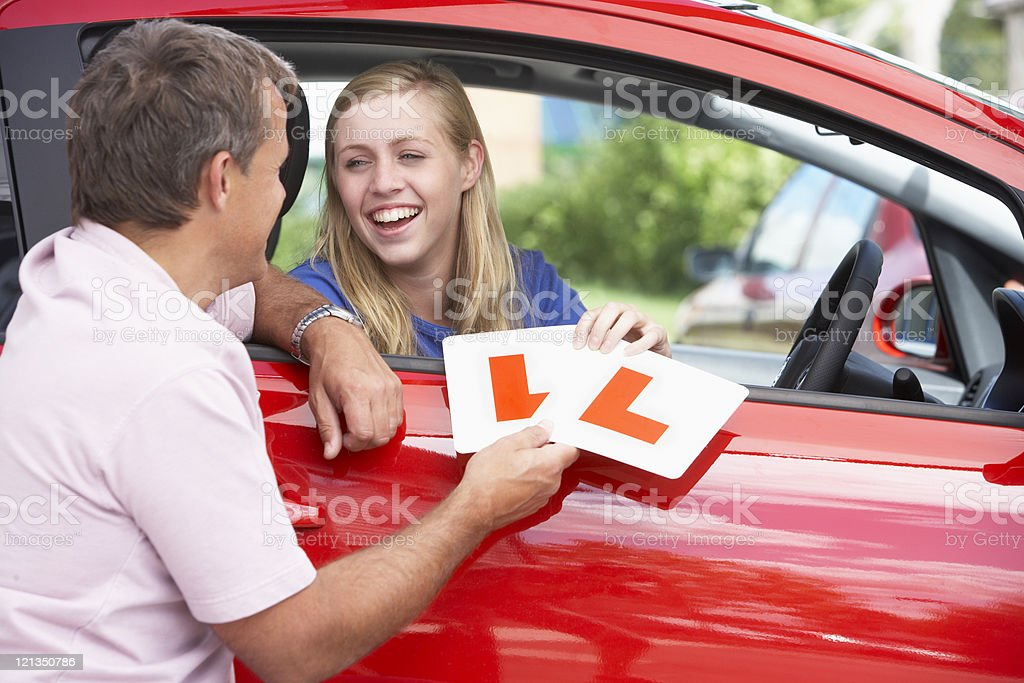 Teenage Girl Receiving Her Learner Plates stock photo