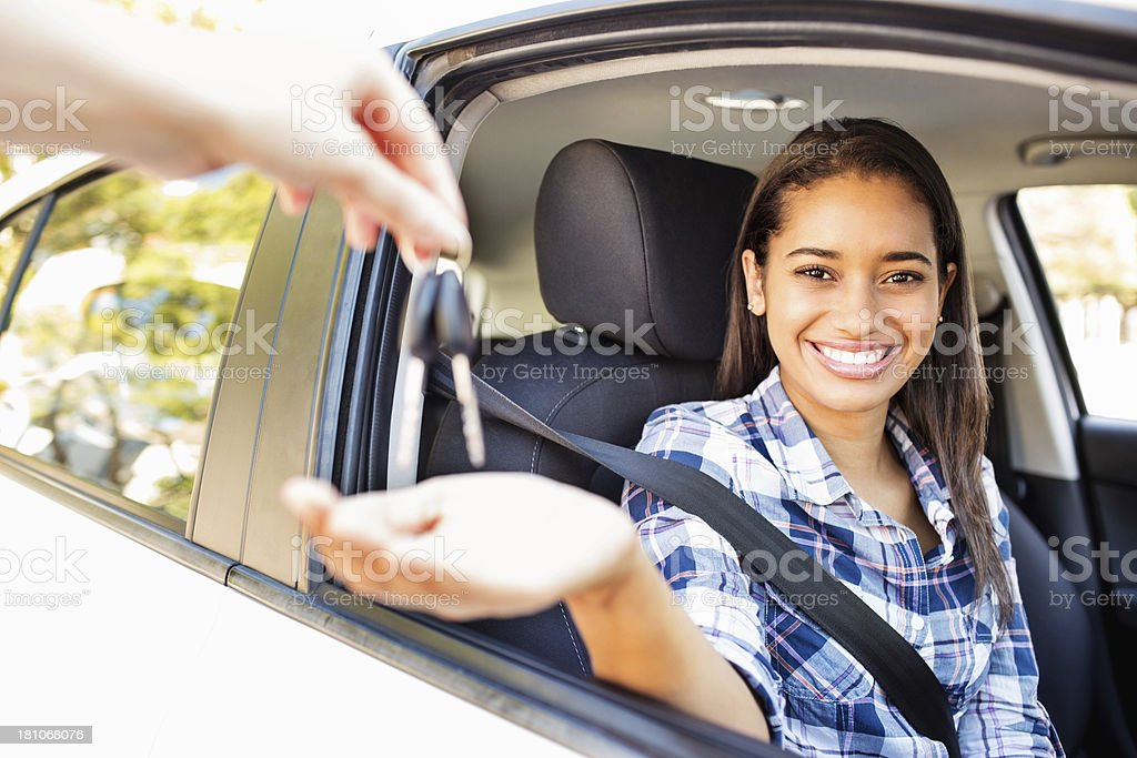 Teenage Girl Receiving Keys While Sitting In Car stock photo
