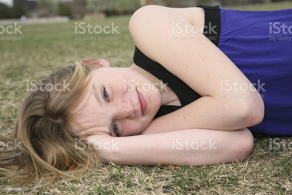 Teenage girl relaxing on the ground at a park royalty-free stock photo