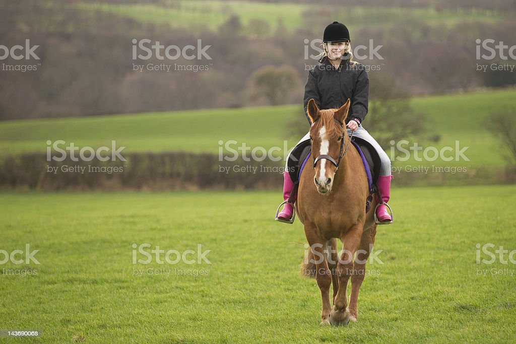 Teenage girl riding horse in field stock photo