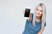 Teenage girl showing a blank smartphone screen