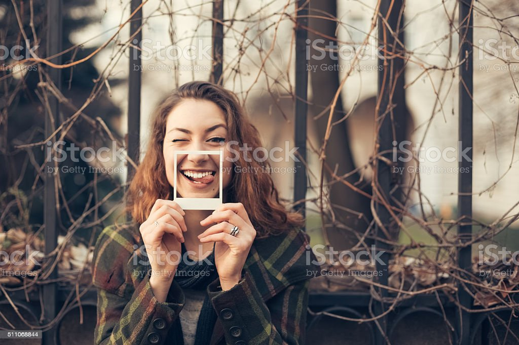 Teenage girl showing funny instant photo stock photo