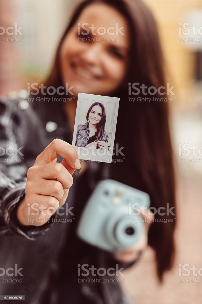Teenage girl showing instant photo stock photo
