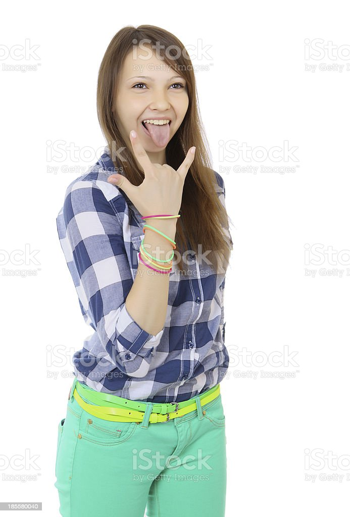 Teenage girl shows tongue and makes hand horns. Mint-colored pants. stock photo