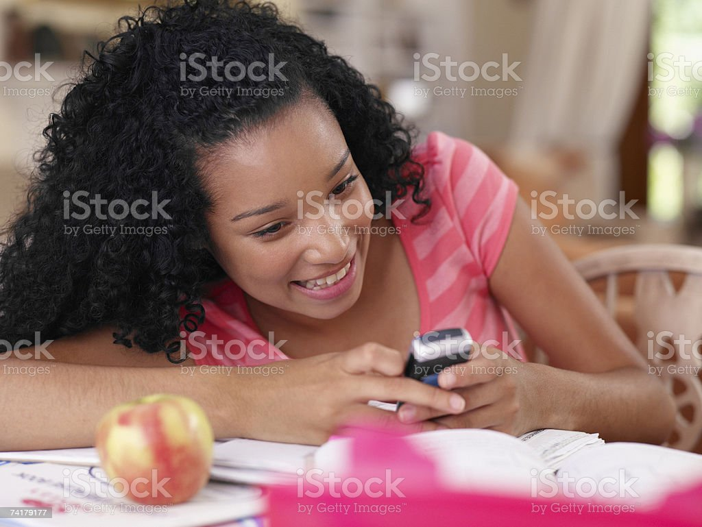 Teenage girl sitting at table with cellular phone and apple royalty-free stock photo