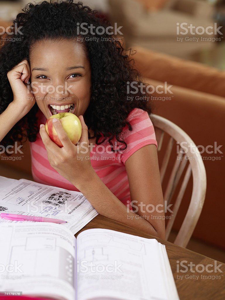 Teenage girl sitting at table with homework eating an apple royalty-free stock photo