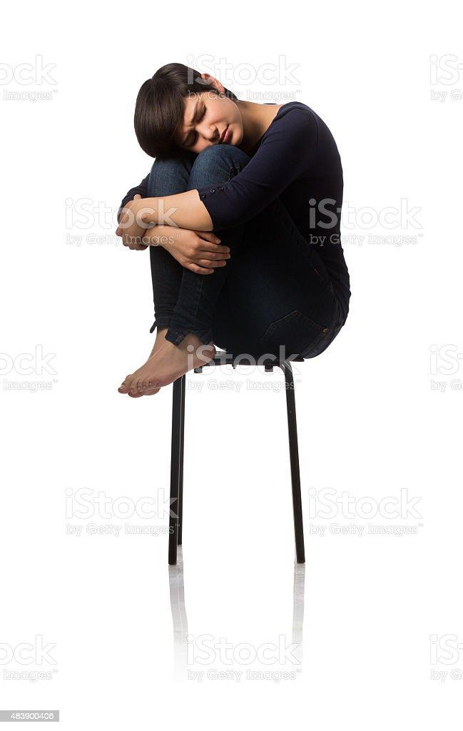 Teenage girl sitting on chair and hugging knees stock photo