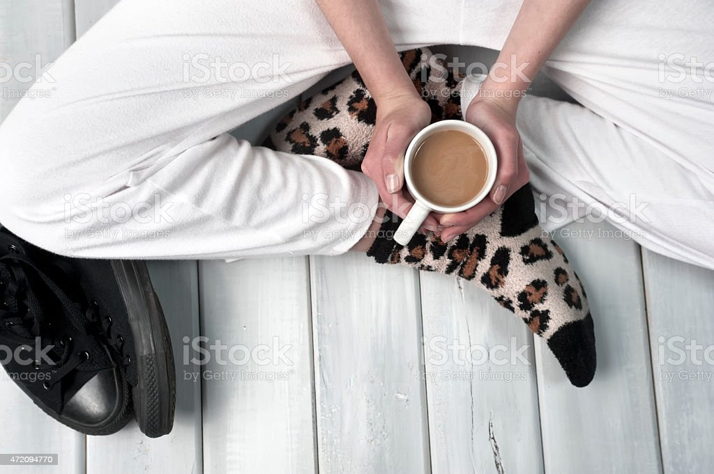 Teenage girl sitting on floor holding a cup of coffee stock photo