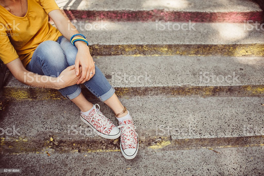 Teenage girl sitting on the stairs stock photo