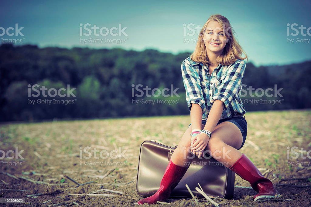 Teenage girl sitting outdoors on old suitcase stock photo