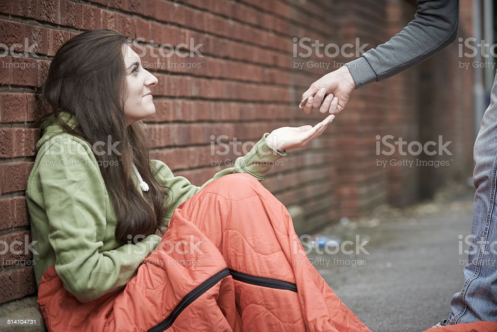 Teenage Girl Sleeping On The Street Being Given Money stock photo