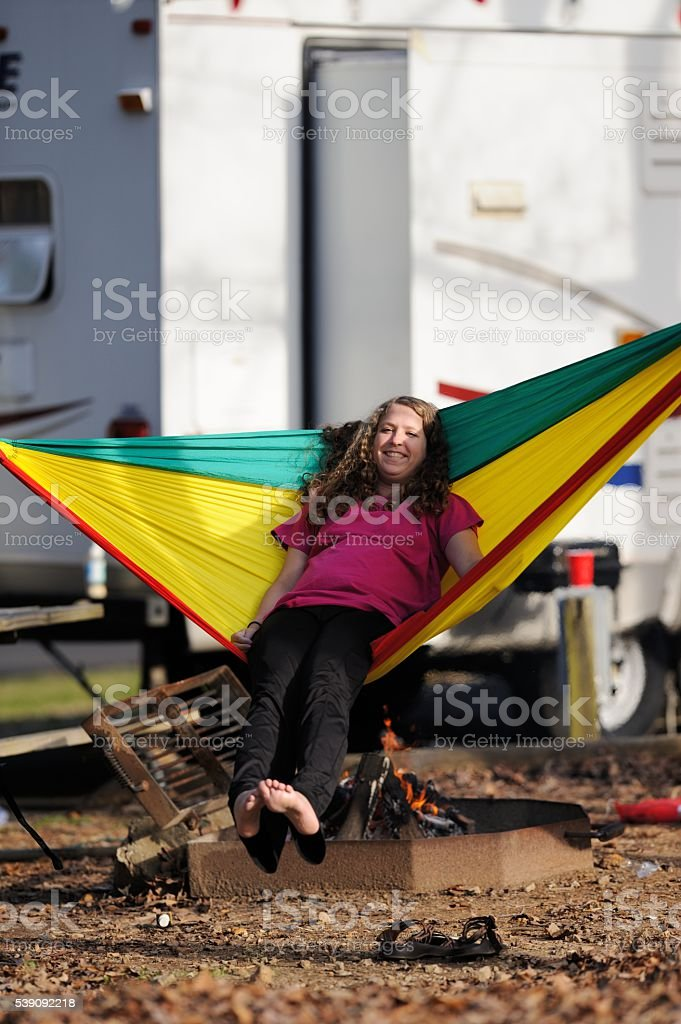 Teenage girl smiling while swinging in hammock at campground stock photo