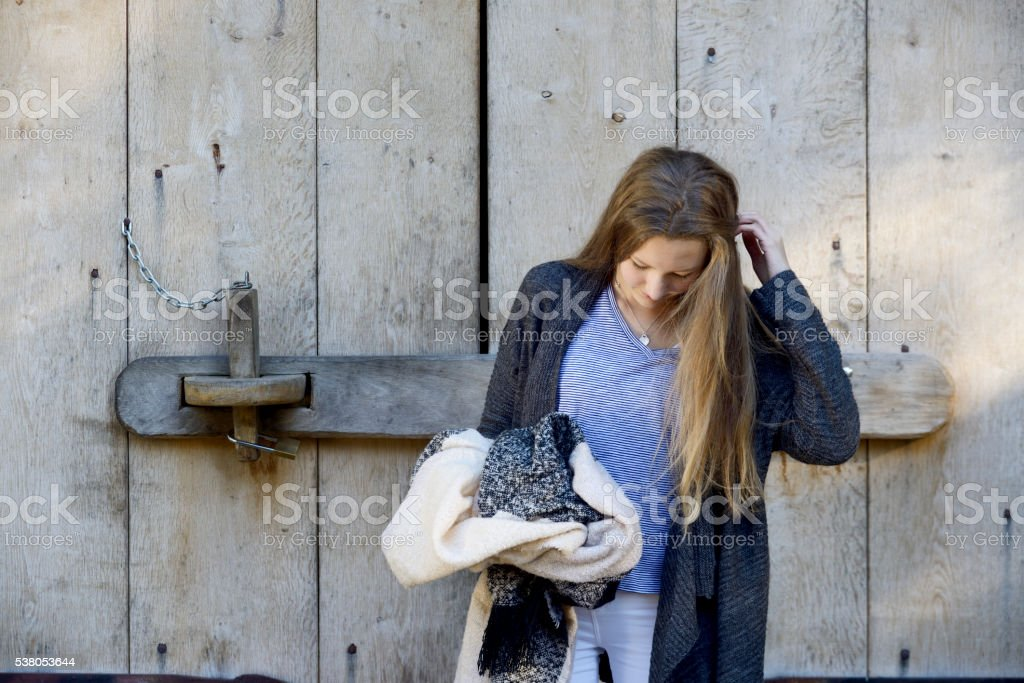 Teenage girl standing at wooden barn doors stock photo