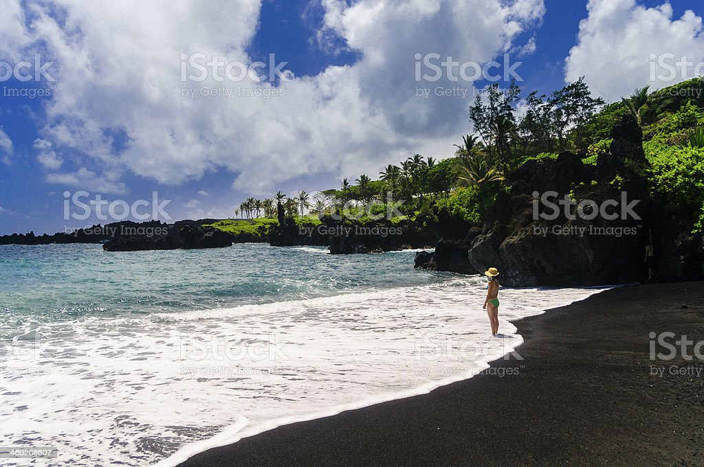 Teenage girl standing in ocean waves on black sand beach. stock photo