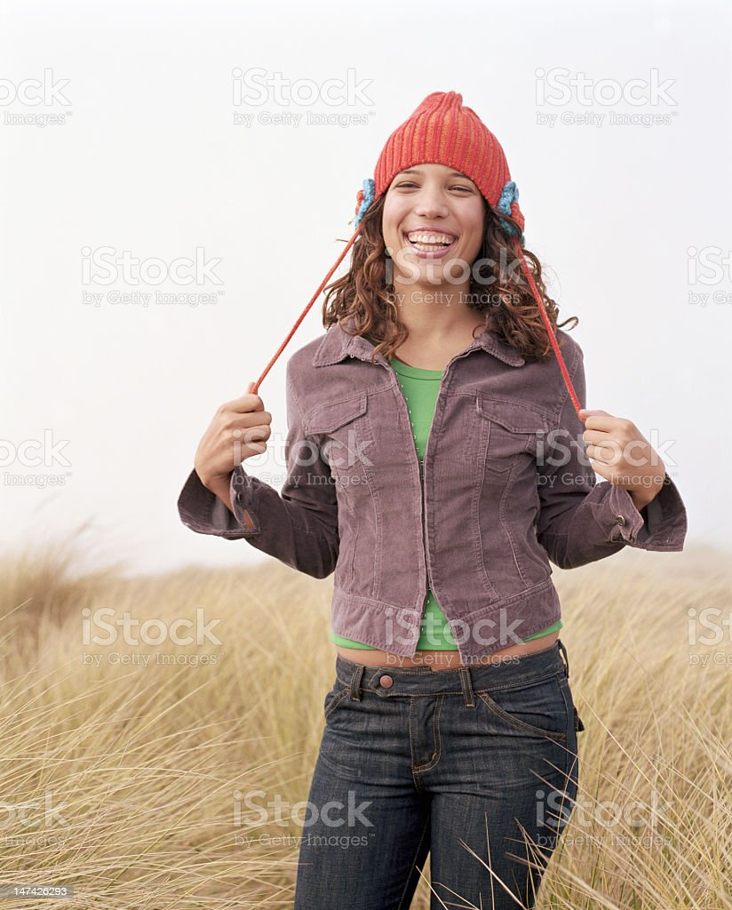 Teenage girl (16-18) standing in tall grass, smiling, portrait stock photo