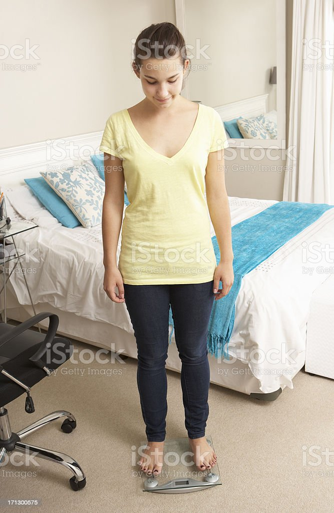 Teenage Girl Standing On Scales In Bedroom royalty-free stock photo