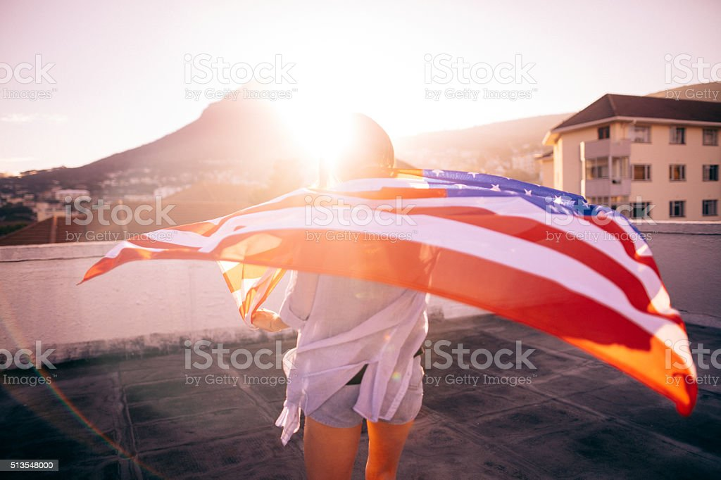 Teenage girl standing with an American flag on rooftop stock photo
