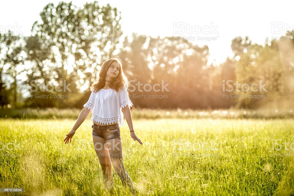 teenage girl standing with arms outstretched in meadow stock photo