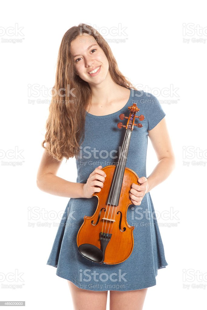 teenage girl stands with violin in studio stock photo