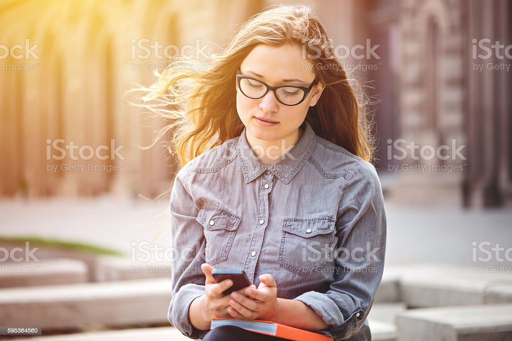 Teenage girl surfing the net on smartphone stock photo