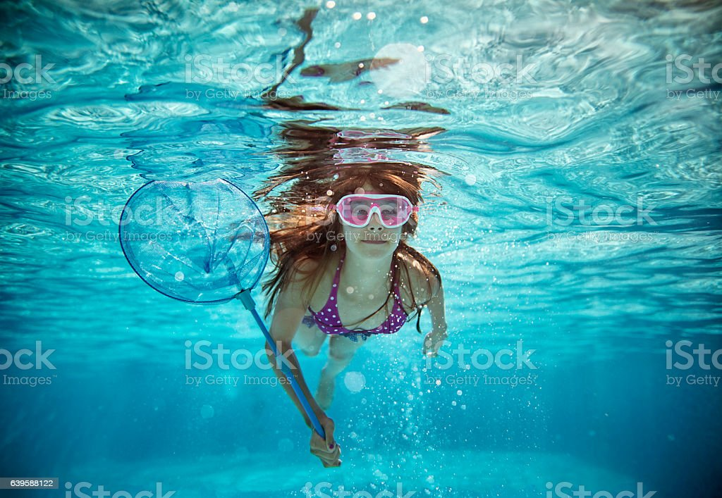 Teenage girl swimming with fish net in pool stock photo