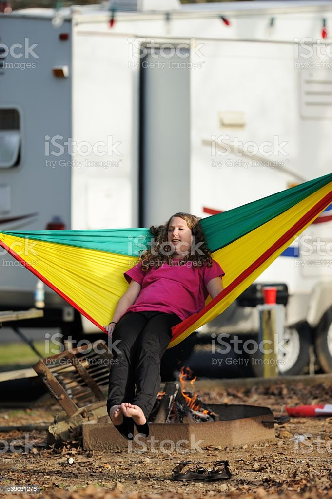 Teenage girl swinging in hammock in campground stock photo