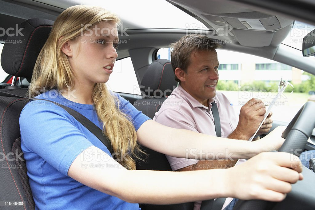 Teenage Girl Taking A Driving Lesson stock photo