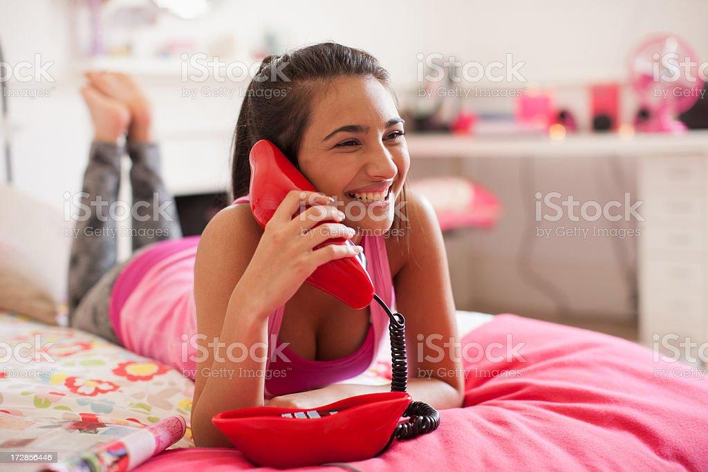 Teenage girl talking on telephone in bedroom stock photo