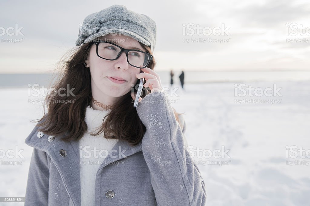 Teenage girl talking via cellphome on the beach stock photo