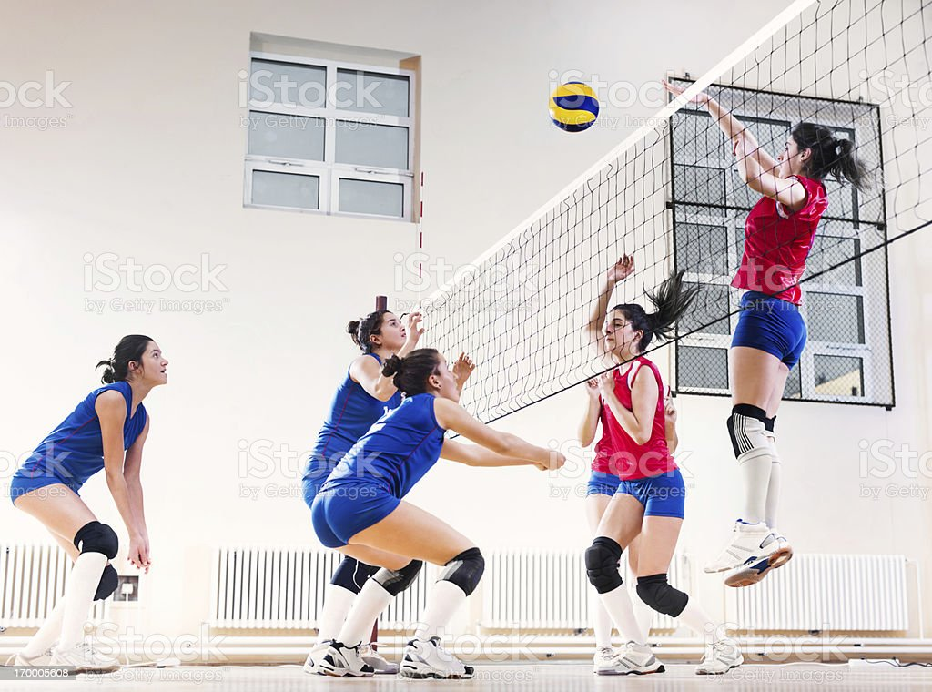 Teenage girl team playing volleyball. stock photo