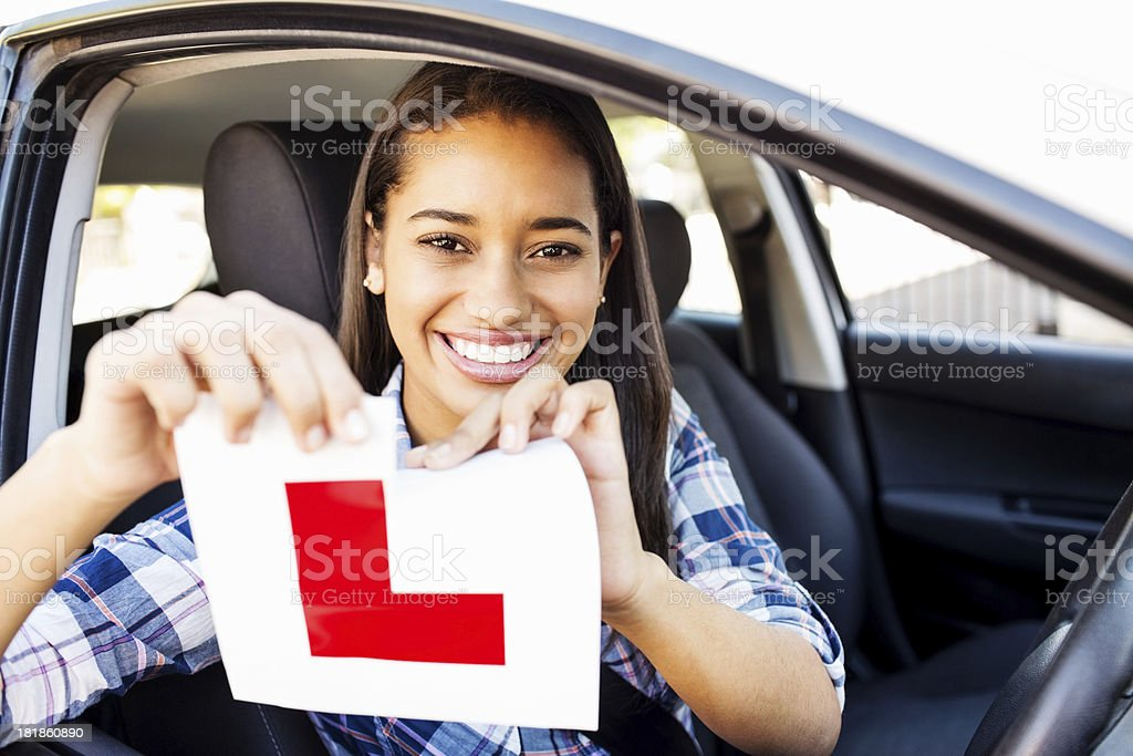 Teenage Girl Tearing L Plate After Passing Driving Test stock photo