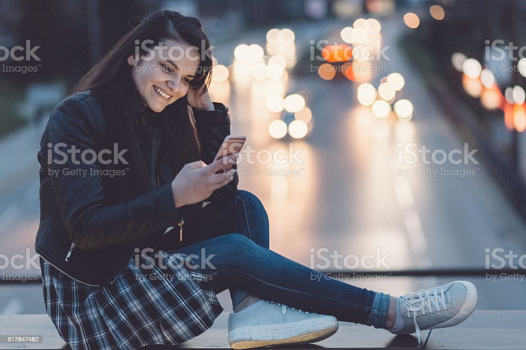 Teenage girl text messaging on smartphone stock photo