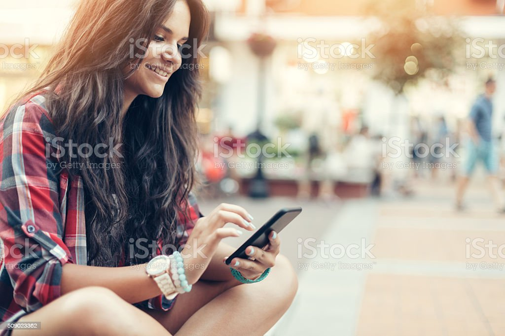 Teenage girl texting at the street stock photo