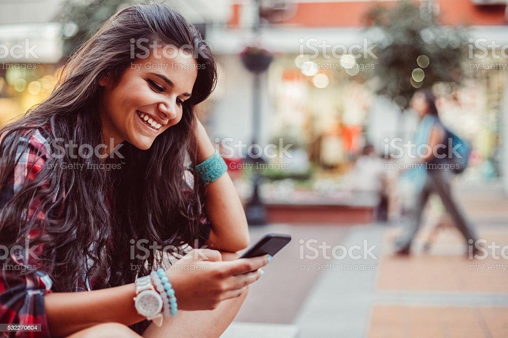 Teenage girl texting for Uber stock photo