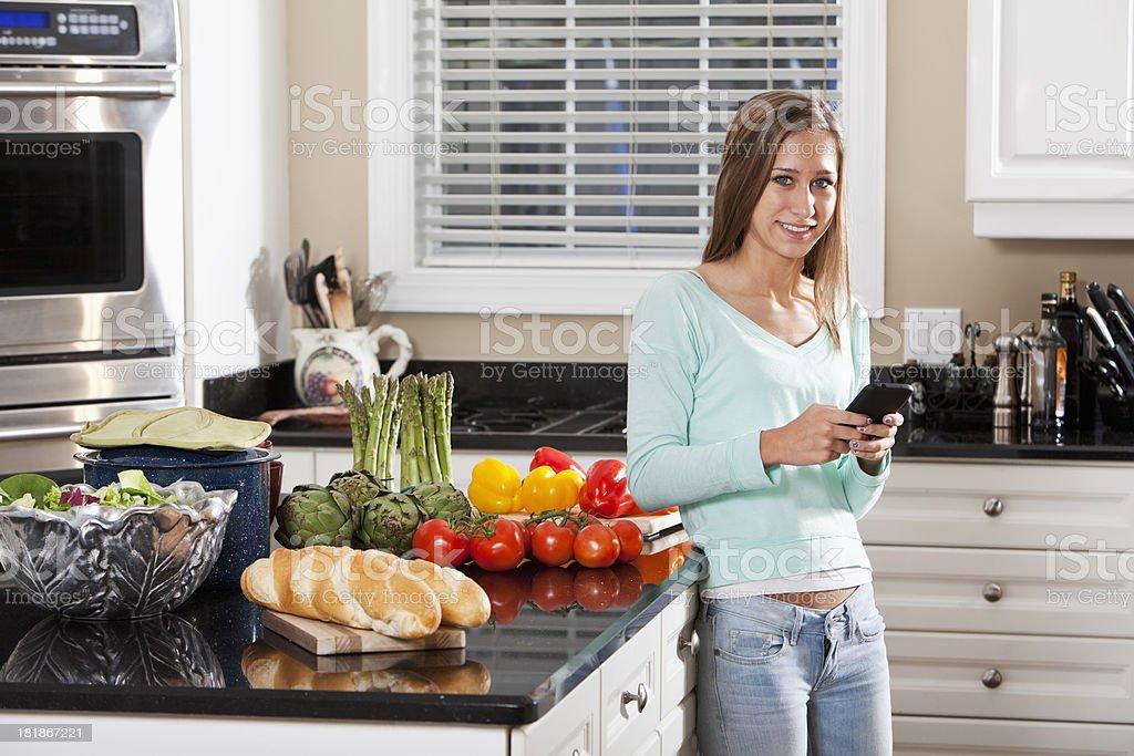 Teenage girl texting in kitchen stock photo