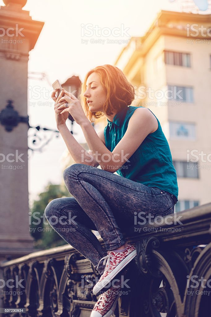 Teenage girl texting on smartphone at the street stock photo