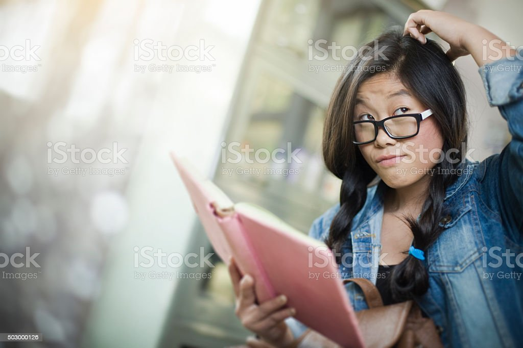 Teenage girl thinking and giving side glance while holding book. stock photo
