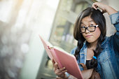 Teenage girl thinking and giving side glance while holding book.