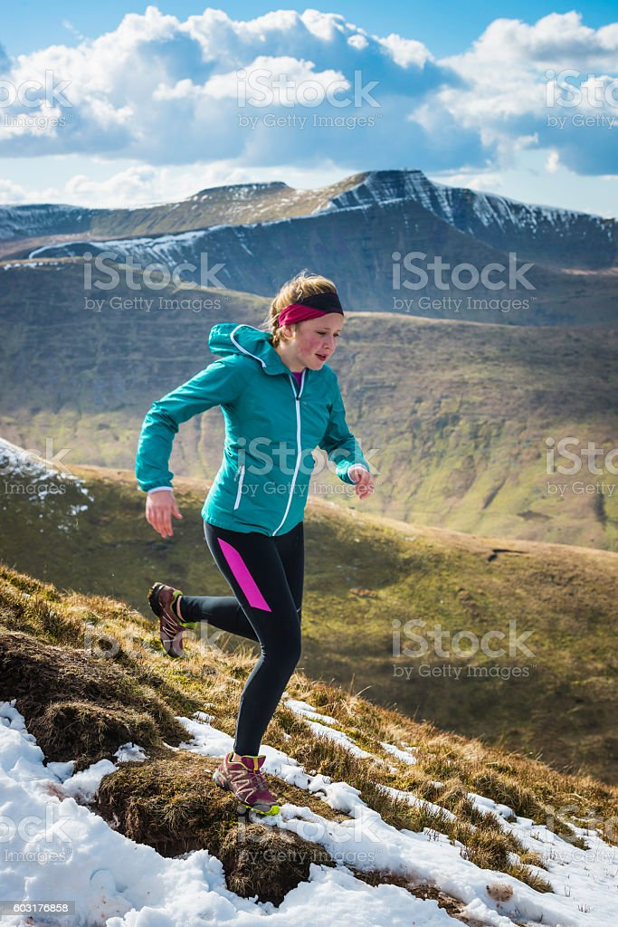 Teenage girl trail running snowy mountain ridge Brecon Beacons Wales stock photo