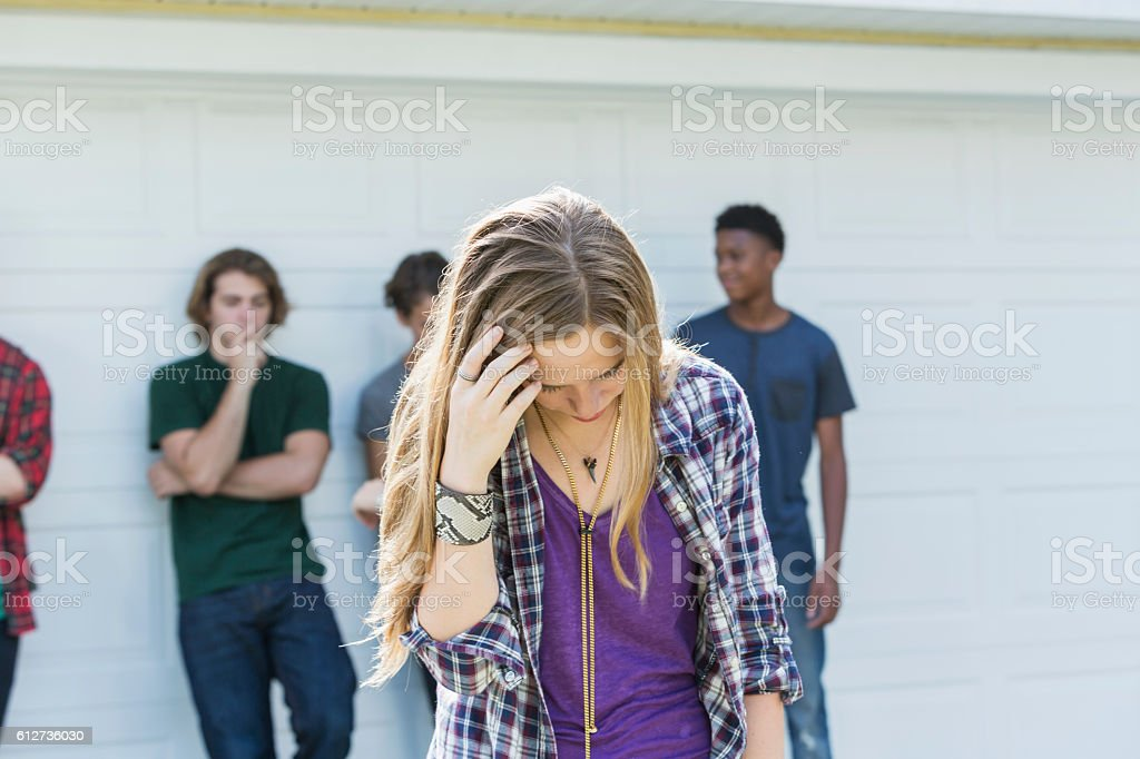 Teenage girl upset looking down, young men in background stock photo