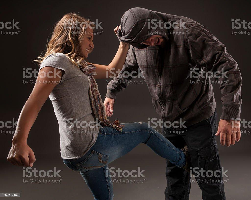 Teenage girl uses self defense skills to fight back. stock photo