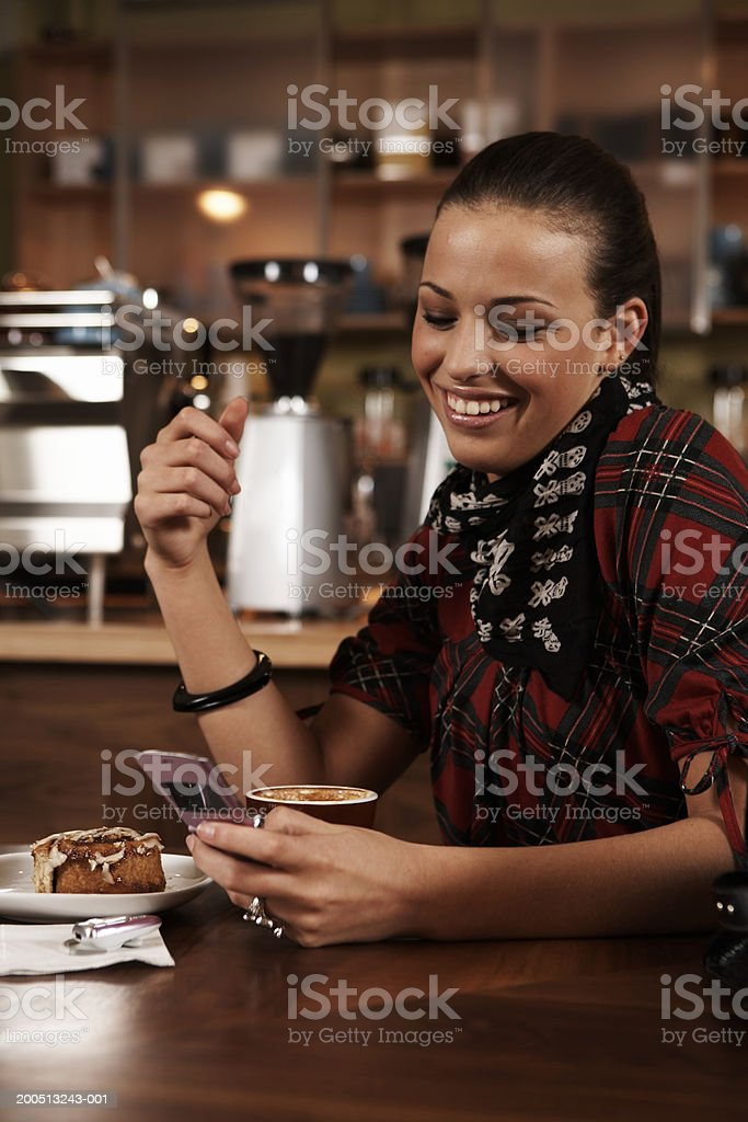 Teenage girl (15-17) using cell phone in cafe, smiling stock photo