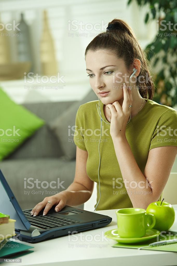 Teenage girl using computer at home royalty-free stock photo