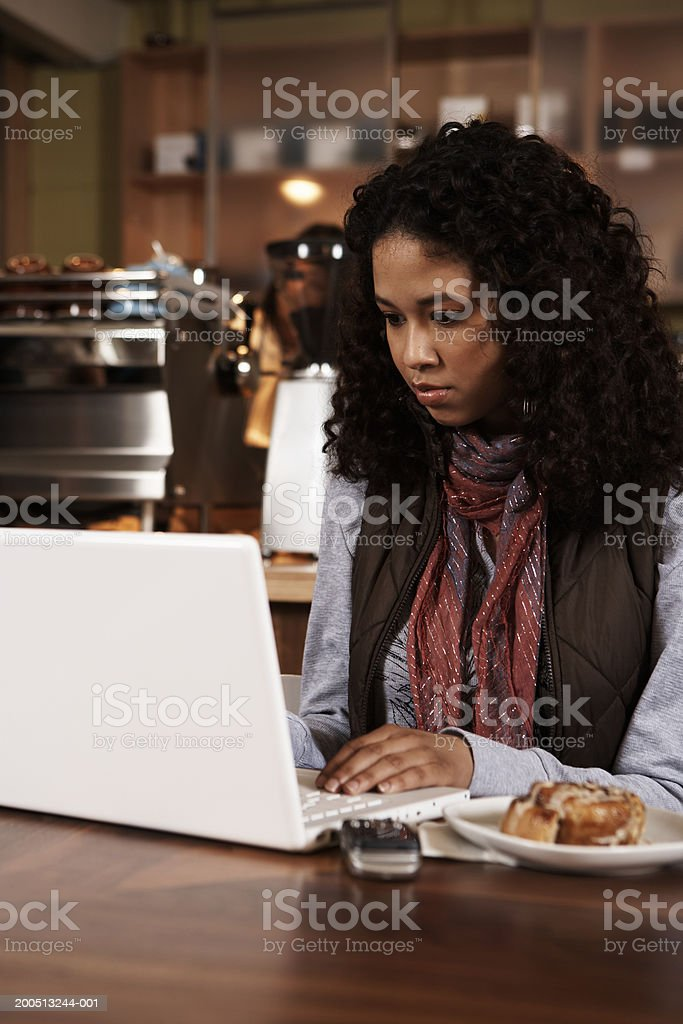 Teenage girl (16-18) using laptop at table in cafe royalty-free stock photo