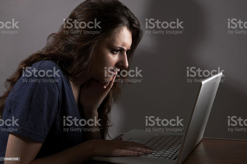 Teenage Girl Using Laptop With Menacing Shadow In Background stock photo