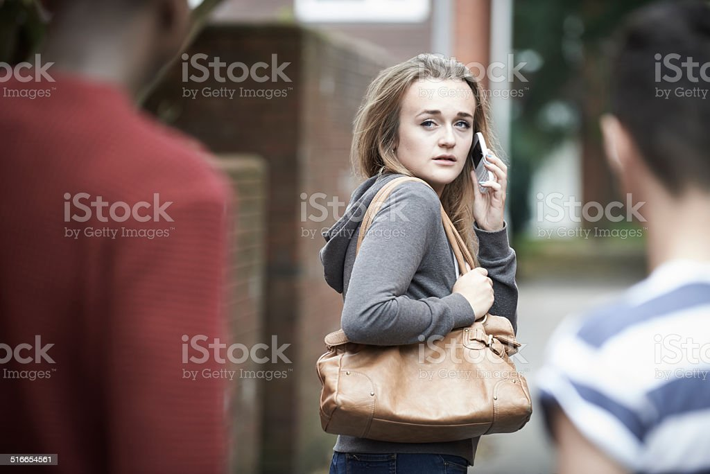 Teenage Girl Using Phone As She Feels Intimidated stock photo