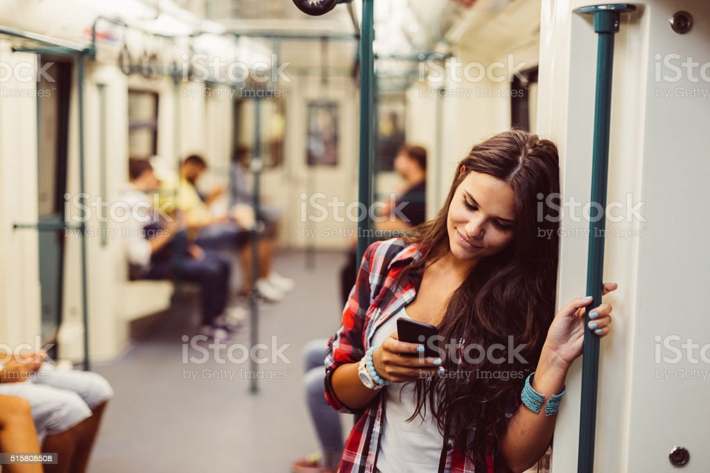 Teenage girl using phone in the subway train stock photo
