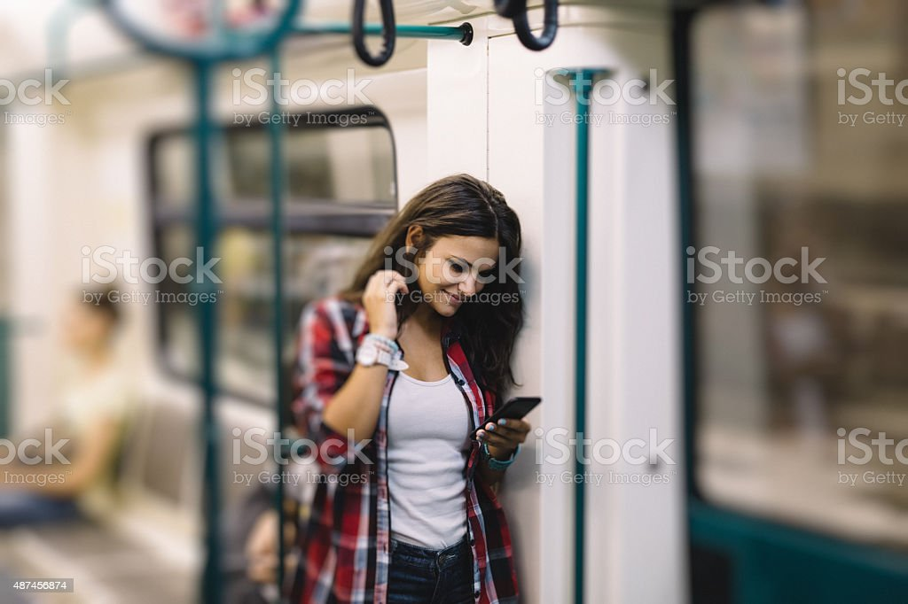 Teenage girl using phone while travelling in the subway train stock photo