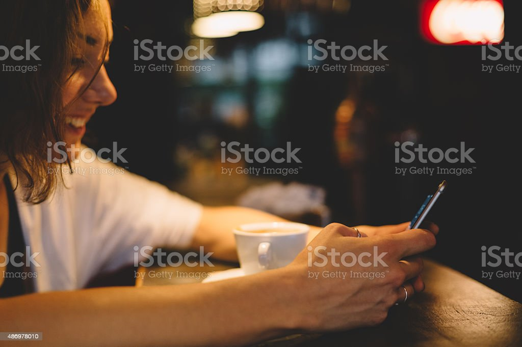 Teenage girl using smartphone in a cafe stock photo