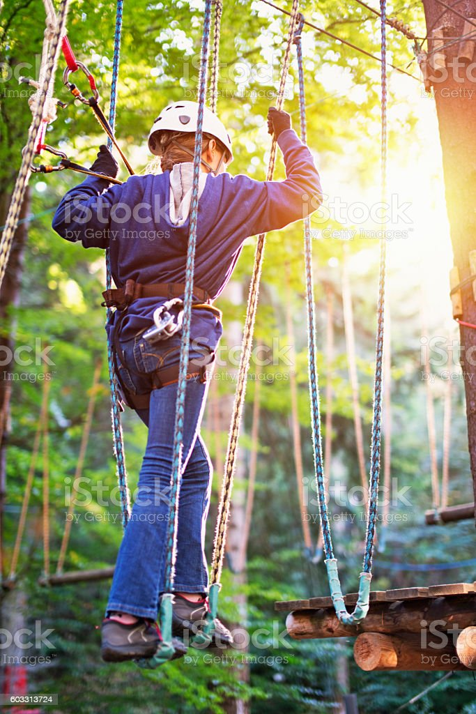 Teenage girl walking in ropes course adventure park stock photo